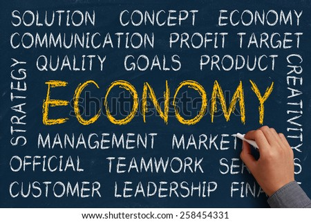 Economy word cloud is written on blue chalkboard by the hand of a businessman. - stock photo