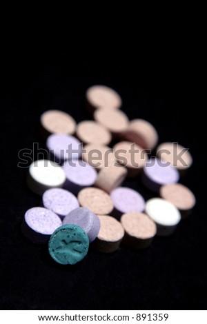 Ecstasy tablets on black background - stock photo