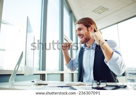 Ecstatic businessman looking at computer monitor in office - stock photo