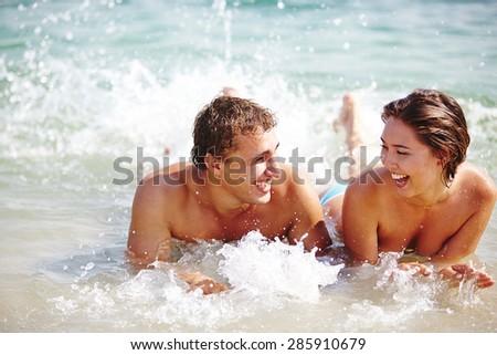 Ecstatic couple splashing in water - stock photo