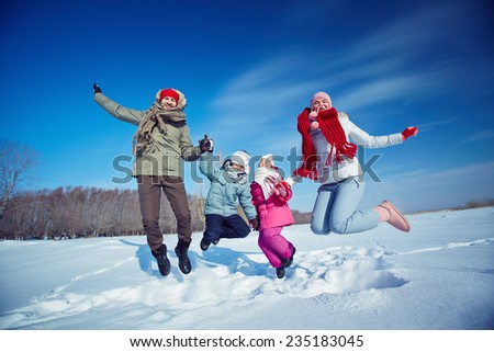 Ecstatic family of four jumping in snow - stock photo