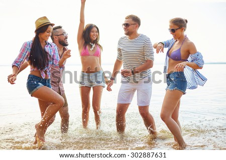 Ecstatic friends dancing in water during vacations - stock photo