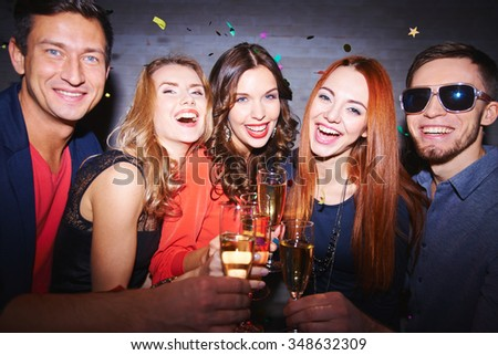 Ecstatic friends toasting with champagne at party - stock photo
