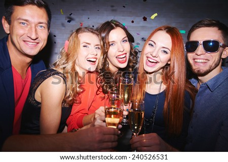 Ecstatic friends with champagne having party - stock photo