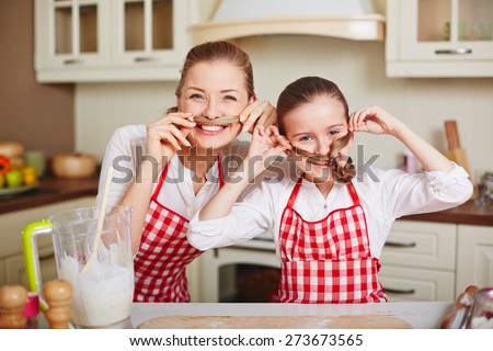Ecstatic girl and her mother in aprons keeping ends of their pigtails by noses - stock photo