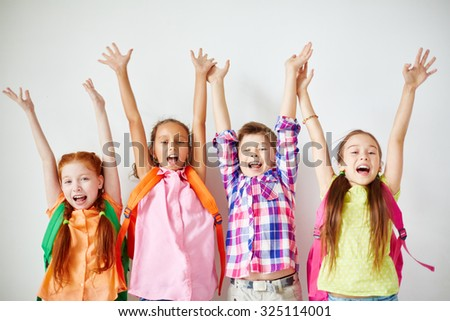Ecstatic kids with backpacks raising their arms