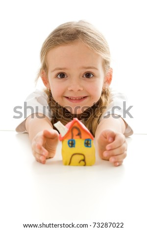 Ecstatic little girl with her clay house grimacing happily - isolated - stock photo
