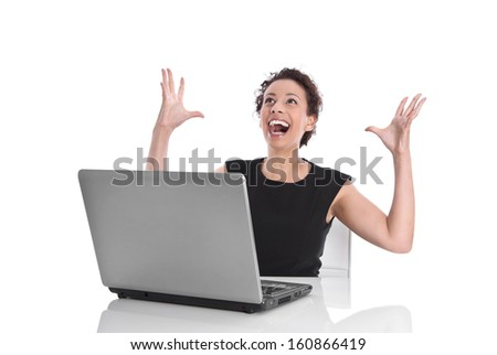 Ecstatic pretty woman sitting at desk with laptop and stretched out arms  isolated on white background