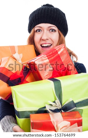 Ecstatic woman in winter hat holding many presents, isolated on white background. - stock photo