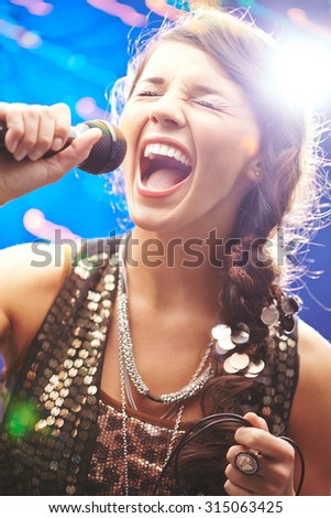 Ecstatic woman singing in mike with her eyes closed - stock photo