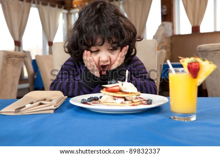 Ecstatic young boy eating a stack of pancakes - stock photo