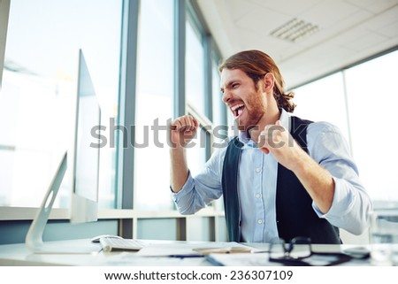 Ecstatic young businessman expressing great satisfaction while looking at computer monitor - stock photo