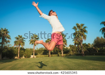 ecstatic young casual man jumping of joy in an exotic garden with palm trees in hte background - stock photo