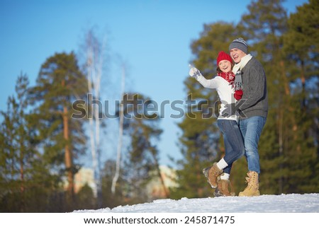 Ecstatic young couple in winterwear spending leisure in park - stock photo