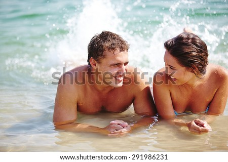 Ecstatic young couple splashing in water during vacations - stock photo