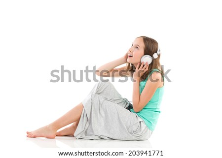 Ecstatic young girl with headphones is sitting on the floor and listening to the music. Full length studio shot isolated on white. - stock photo