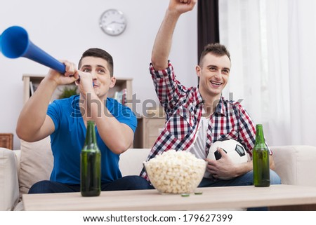Ecstatic young men supporting soccer at home  - stock photo
