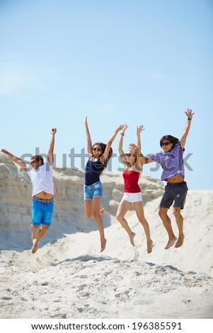 Ecstatic young people holding by hands while jumping over sandy beach - stock photo