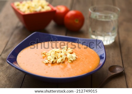 Ecuadorian tomato and potato cream soup served with popcorn on top (Selective Focus, Focus on the front of the popcorn on the soup) - stock photo