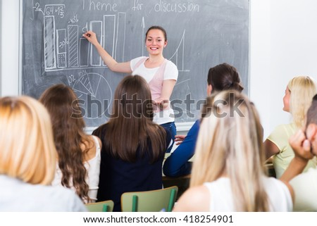 Ecxited young student gives answer near blackboard during lesson - stock photo