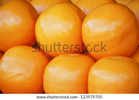 Edam is a Dutch cheese traditionally sold in spheres with a pale yellow interior and a coat of red paraffin wax - stock photo