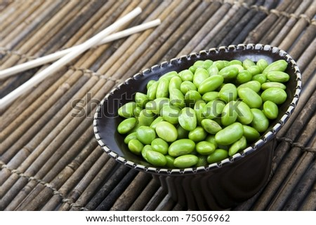 Edamame soy beans in a brown ceramic dish with chopsticks. - stock photo