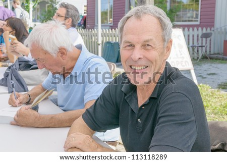 EDEN MILLS, ON - SEPTEMBER 16:  Canadian writers and broadcasters, Linden McIntyre and Richard Gwyn, sign their books at the annual Writers Festival in Eden Mills, Ontario on September 16, 2012. - stock photo