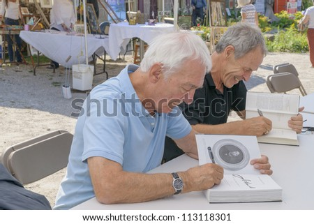 EDEN MILLS, ON - SEPTEMBER 16:  Canadian writers and broadcasters, Richard Gwyn and Linden McIntyre, sign their books at the annual Writers Festival in Eden Mills, Ontario on September 16, 2012. - stock photo
