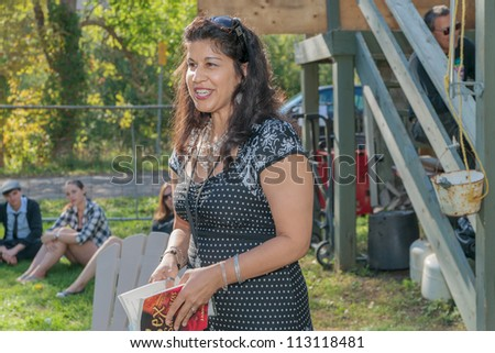 EDEN MILLS, ON - SEPTEMBER 16:  Indo-Canadian writer, Jasmine Adiz, reads from her first book at the annual Writers Festival in Eden Mills, Ontario on September 16, 2012. - stock photo