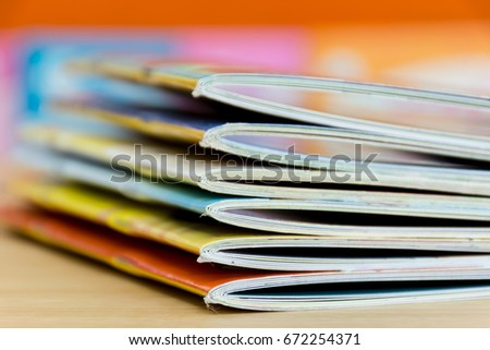 edge book on the wooden table.   Stack magazines with  bookshelf blurred background,  education concept.