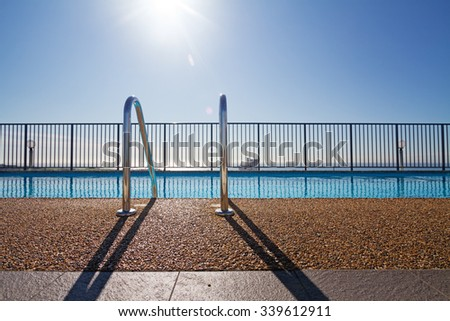Edge of swimming pool and ladder with sun flare in background - stock photo