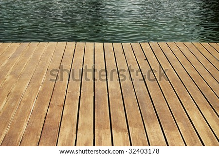 edge of wood deck near water - stock photo