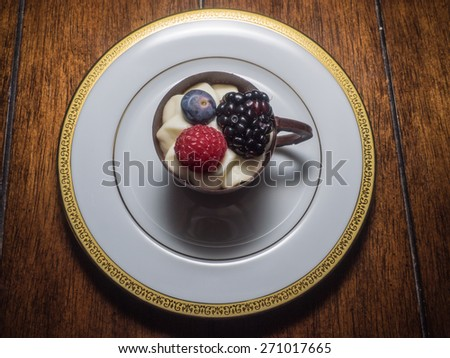 Edible chocolate cup filled with cream and topped with fruits - stock photo