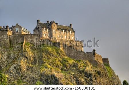Edinburgh Castle on Castle Rock in the light of the setting sun - stock photo