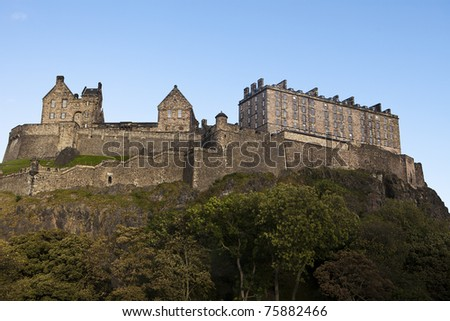 Edinburgh Castle rises above the city protected by natural cliffs and high rock walls. The guards' stone barracks and other buildings are all part of the landmark structure. - stock photo