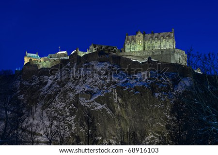 Edinburgh Castle, Scotland, UK, illuminated at dusk with winter snow - stock photo