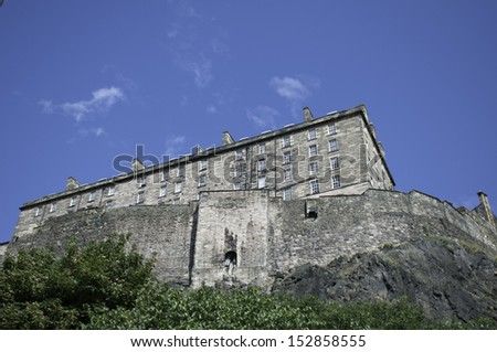 Edinburgh Castle was built on an extinct volcano, this photograph shows the rear of the castle and the rock base of the castle above the trees - stock photo