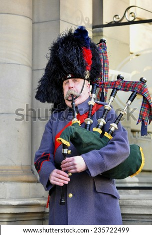 EDINBURGH - DEC 29: Unidentified Scottish Bagpiper playing music with bagpipe at Edinburgh on December 29.2013 in Scotland. - stock photo