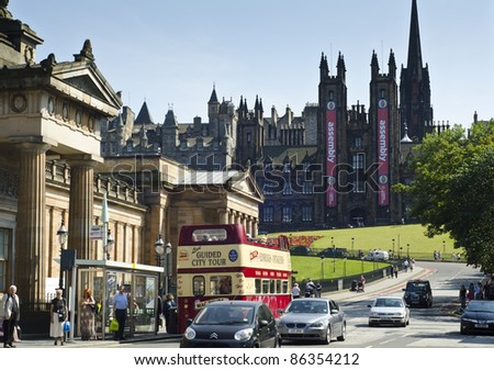 EDINBURGH - JULY 30: a vintage tour bus at The Mound with the Free Church of Scotland behind on July 30, 2011 in Edinburgh, Scotland. Edinburgh is the UK's second most visited tourist destination. - stock photo