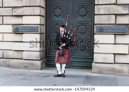 EDINBURGH - MAY 02:A bagpiper plays music in front of the High Court of Edinburgh building on May 02, 2013 in Edinburgh, Scotland, UK. Edinburgh is the most popular tourist destination in Scotland. - stock photo