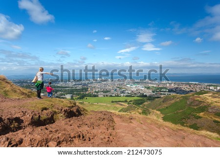 EDINBURGH, SCOTLAND: AUGUST 4, 2014: Tourist pointing finger in distance on Arthur's seat in Holyrood Park. Arthur's seat is popular destination for hiking and enjoying nature.  - stock photo