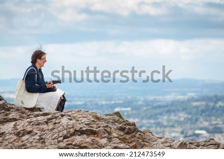 EDINBURGH, SCOTLAND: AUGUST 4, 2014: Woman photographer enjoying the view from the Arthur's seat in Holyrood Park. Arthur's seat is popular destination for hiking and enjoying nature.  - stock photo