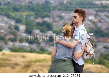 EDINBURGH, SCOTLAND: AUGUST 4, 2014: Young couple enjoying the view from the Arthur's seat in Holyrood Park. Arthur's seat is popular destination for hiking and enjoying nature.  - stock photo