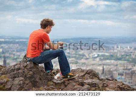 EDINBURGH, SCOTLAND: AUGUST 4, 2014: Young man eating blueberries and enjoying the view from the Arthur's seat in Holyrood Park. Arthur's seat is popular destination for hiking and enjoying nature.  - stock photo