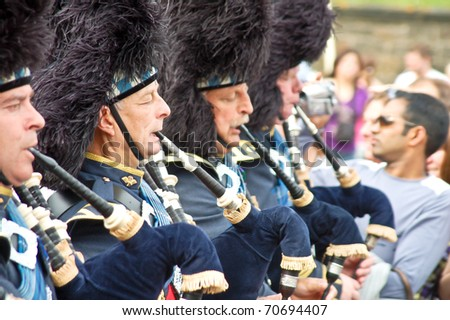EDINBURGH, SCOTLAND - CIRCA AUGUST 2009: A group of Scottish pipers play their traditional music during the annual Festival parade circa August 2009 in Edinburgh, Scotland. - stock photo