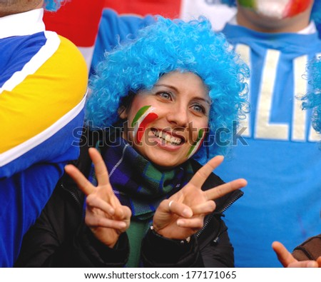 EDINBURGH, SCOTLAND-MARCH 26, 2007: Italian woman fan wearing a blue wig, supports the Italian team ,during the Six Nations Rugby Tournament match Scotland vs Italy. - stock photo