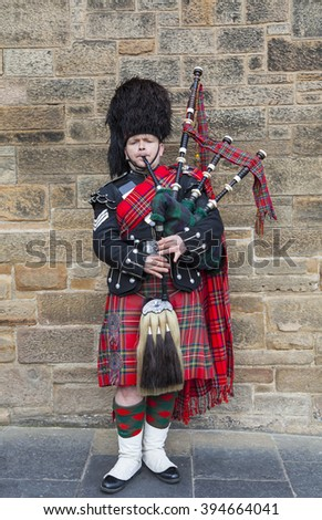 EDINBURGH, SCOTLAND - MARCH 8TH 2016: A Scotsman wearing traditional Scottish outfit playing the bagpipes along the Royal Mile in Edinburgh, on 8th March 2016. - stock photo
