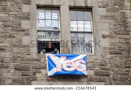 EDINBURGH, SCOTLAND - SEPTEMBER 11, 2014: An elderly man smiling from the window of his Edinburgh flat which is covered in Yes posters supporting Scottish independence in next week's referendum. - stock photo