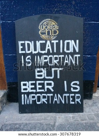 EDINBURGH, SCOTLAND, UK - CIRCA AUGUST 2015: Education is important but beer is importanter, funny pun wooden sign label before a pub - stock photo