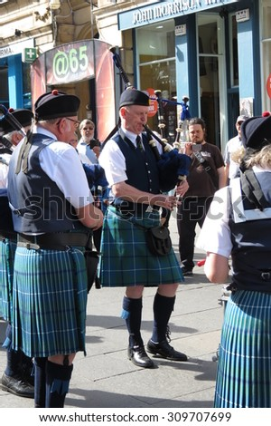 EDINBURGH, SCOTLAND, UK - CIRCA AUGUST 2015: Scottish bagpipers dressed in traditional green, blue and black tartan dress - stock photo